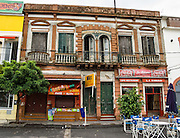 "An old building with balconies and streetside cafe. In La Boca barrio (neighborhood) of Buenos Aires, tourists are attracted by colorful houses, the Caminito pedestrian street, La Ribera theatre, tango clubs, and Italian taverns. La Boca retains a strong European flavor, with many early settlers from Genoa, Italy. It sits at the mouth (""boca"" in Spanish) of the Matanza River (or Río Mataderos, or Riachuelo which simply means ?Creek?). La Boca is known among sports fans for La Bombonera stadium (Estadio Alberto J. Armando), home of Boca Juniors, one of the world's best known football (soccer) clubs. As a centre for radical politics, La Boca elected the first socialist member of the Argentine Congress (Alfredo Palacios in 1935) and hosted many demonstrations during the crisis of 2001 in Argentina, South America."