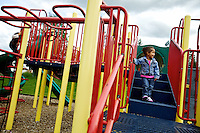 Aryana Fielder, 2, enjoys the view from the playground equipment at Thayer Park in Rathdrum during an outing Thursday with her father and brother.