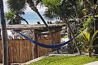 terrace of a cabana with a hamac and a view of the beautiful white sand beach of tulum in yucatan mexico