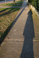 Long photographers shadow on footpath in urban Dublin Ireland with evening winter sunlight
