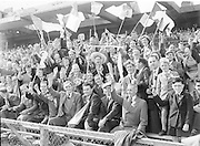 Smiling supporters waving flags in the stands during the All Ireland Senior Gaelic Football final Dublin vs Derry in Croke Park on 28th September 1958. Dublin 2-12 Derry 1-9.