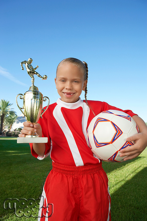 Girl (7-9 years) soccer player holding trophy and ball, portrait