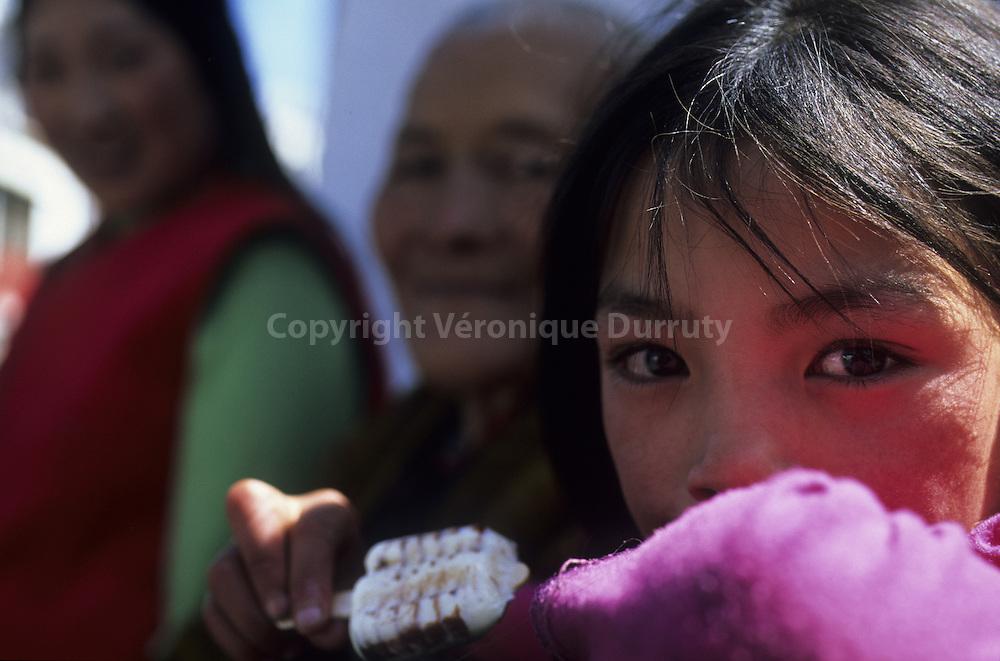 GIRL EATING ICE CREAM. TIBETAN PILGRIMS FAMILY IN LHASA, TIBET, China // Adolescente mangeant une glace. Famille de pélerins tibétains à LHASSA, TIBET, Chine