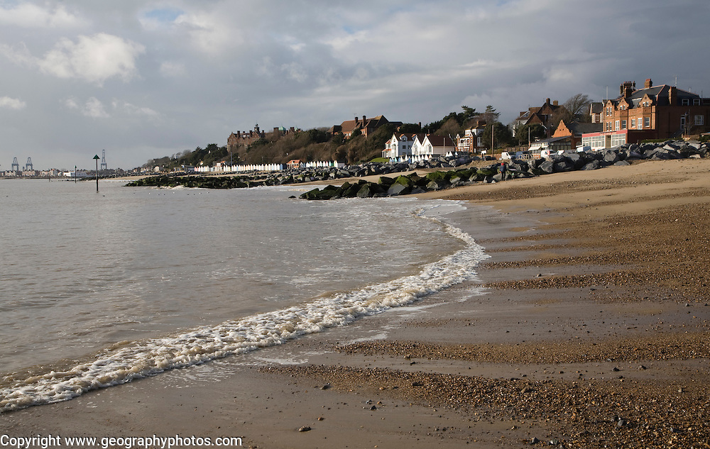 Sandy beach, rock groynes, seaside beach huts and buildings, Felixstowe, Suffolk, England