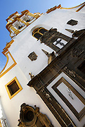 Oblique low angle view of the Parish Church of Santa Cruz, Seville, Spain, pictured on December 30, 2006, in the afternoon. Located on Calle Mateos Gago this 17th century church replaces an earlier church on the Plaza de Santa Cruz which gave the area its name. Architectural details are picked out in gold against the white washed walls. Picture by Manuel Cohen.