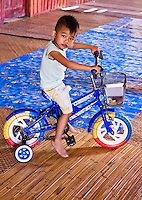 Little boy at Nanga Sumpa longhouse shows off his new bike.