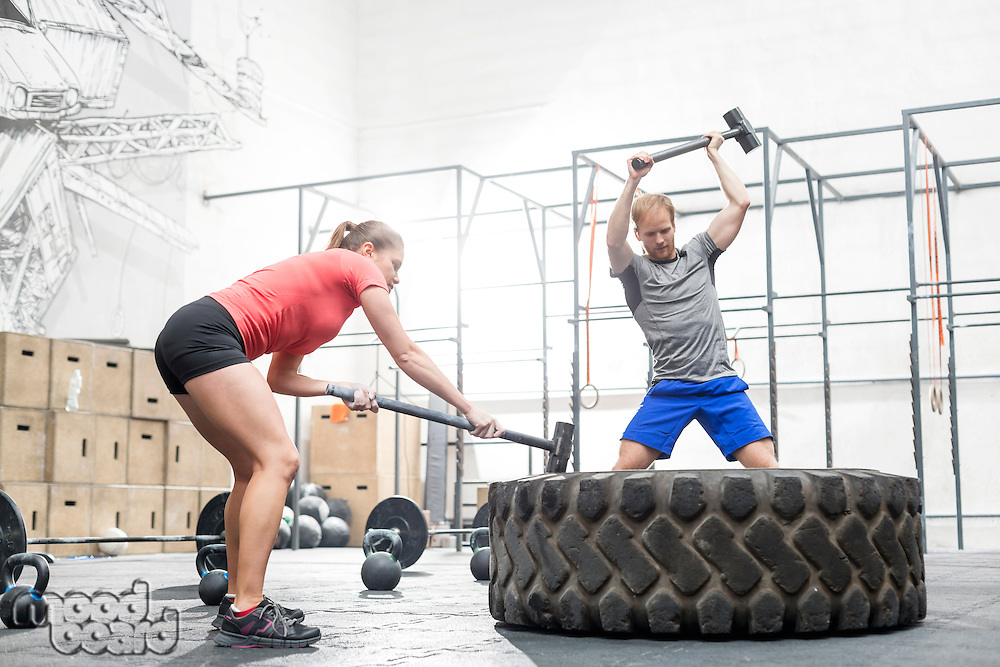 Man and woman hitting tire with sledgehammer in crossfit gym