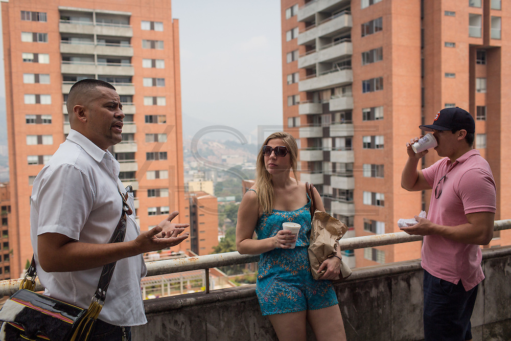 "30/03/2016 - Medellin, Colombia: Carlos Palau, a tour guide and former policeman, talks with two American tourists, Elizabeth Wilky, 34, and Miguel Nuñez, 34,  on the balcony of the Pablo Escobar's penthouse in Monaco building, Medellin. Tours focusing on the life and death of Pablo Escobar are becoming quite popular among international tourists that visit Medellín. In recent times more than 10 tour operators have started to give the tour, helped by the interest generated by Netflix ""Narcos"" series. (Eduardo Leal)"