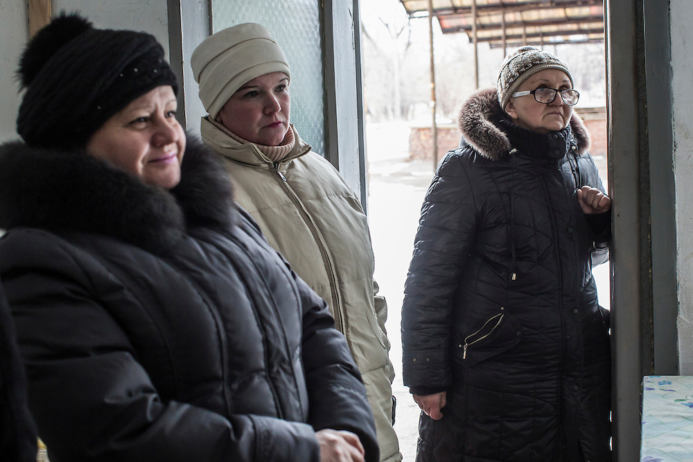 NYZHNIA KRYNKA, UKRAINE - JANUARY 27, 2015: Olga Zaytseva, right, and other customers at a shop selling basic staples in Nyzhnia Krynka, Ukraine. After intense fighting in the area over the summer, residents of the village are still facing severe difficulties accessing affordable food. CREDIT: Brendan Hoffman for The New York Times