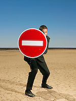 Businessman holding 'no entry' sign in desert full length