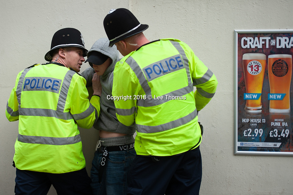 Walsall, West Midlands, UK. 7th April 2018. Pictured:  Police have a quiet word with a young man who attended the EDL rally. / Up to 60 English Defence League supporters take to the streets of Walsall to protest against their claims that the West Midlands town has problems with child exploitation and no-go areas. Scores of police formed a barrier between English Defence League supporters and a vocal anti-fascist contingent, individual protests of which took place only yards away from each other. // Lee Thomas, Tel. 07784142973. Email: leepthomas@gmail.com  www.leept.co.uk (0000635435)