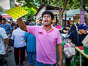 24 NOVEMBER 2018 - BANGKOK, THAILAND:  A tout tries to draw people into a game of Thai Bingo at the Red Cross Fair. The Red Cross Fair is a fund raiser and an annual event in Bangkok that draws thousands of attendees every night of its nine day run. The fair features games of chance, a midway with rides, handicrafts and food. This is the first year the fair has been in Lumpini Park. Previously it had been held in the Dusit section of Bangkok. The 2018 Fair marks 125 years of service for the Red Cross in Thailand.    PHOTO BY JACK KURTZ