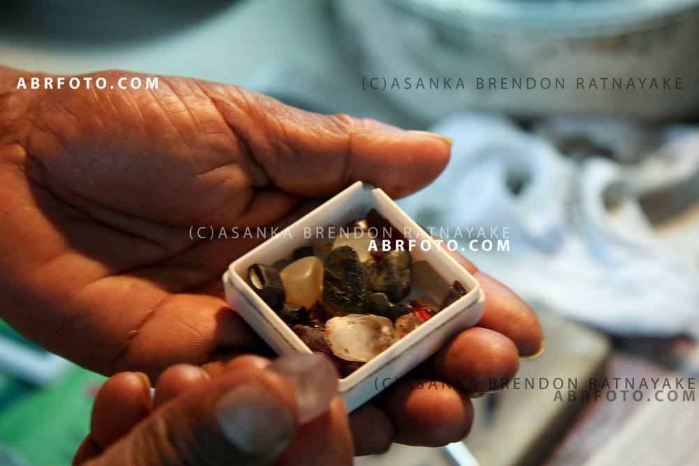 A gem jeweler holds up a collection of Gems in a box to select which ones to chooise to create a piece of Jewellery