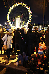 © Licensed to London News Pictures. 31/12/2017. London, UK. Revellers gather to watch the New Year's Eve fireworks at midnight on z London's Embankment. . Photo credit: Peter Macdiarmid/LNP