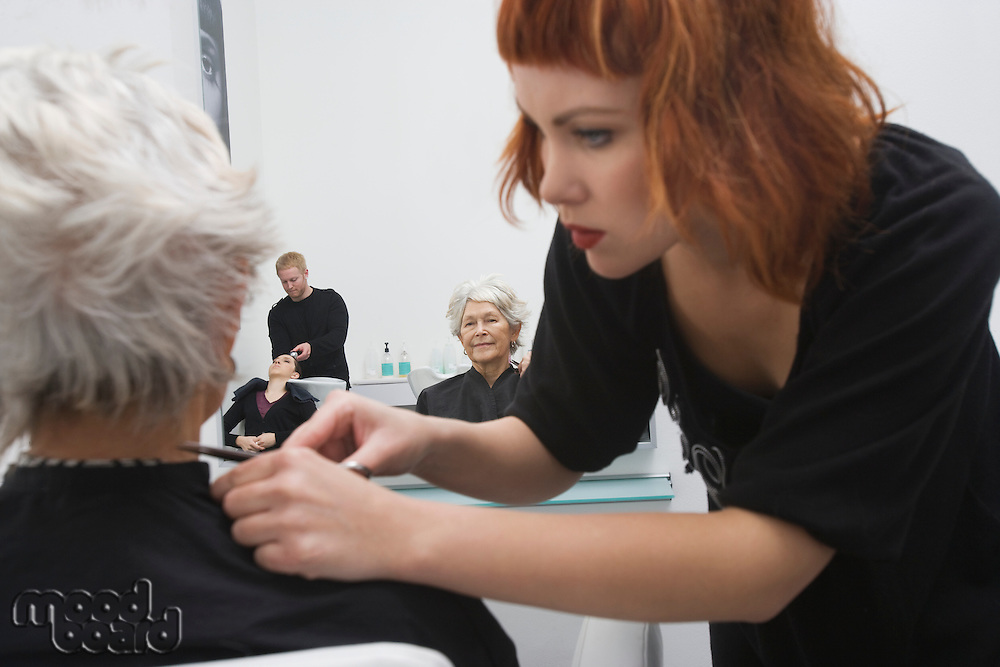 Stylist makes finishing touches to elderly woman's hair