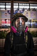 Protestor wearing a full face respirator mask stands on Nathan Road in Kowloon, Hong Kong.<br />
