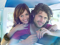 Young couple leaning over back of seat in van