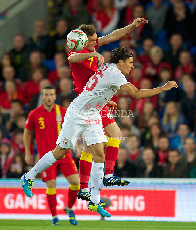 CARDIFF, WALES - Tuesday, September 10, 2013: Wales' Andy King in action against Serbia's Dejan Lekic during the 2014 FIFA World Cup Brazil Qualifying Group A match at the Cardiff CIty Stadium. (Pic by David Rawcliffe/Propaganda)
