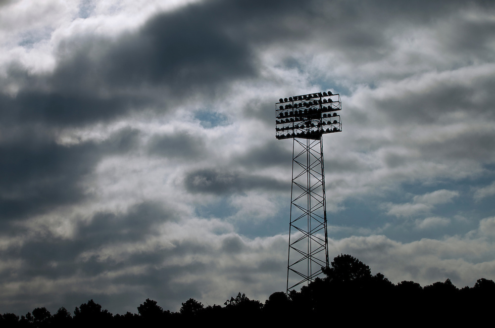 An image of stadium lights at a race track with dramatic clouds and sky.