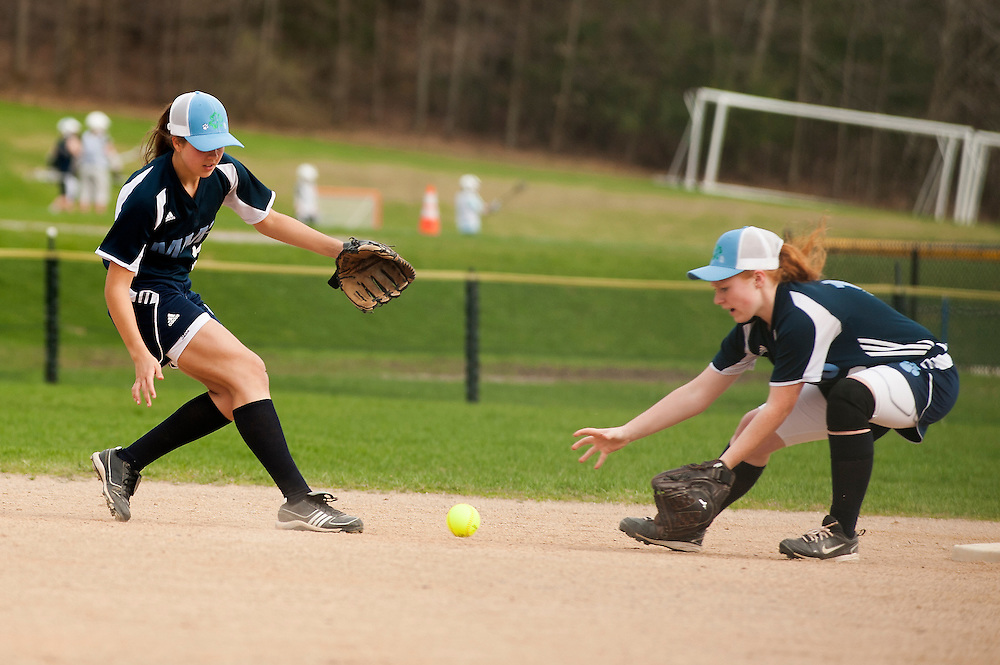 MMU's Danielle Bushey (right) and Felicia Forsyth attempt to field a ground ball during the girls softball game between BFA-St. Albans and Mount Mansfield at MMU High School on Thursday afternoon May 8, 2014 in Jericho, Vermont. (BRIAN JENKINS, for the Free Press)