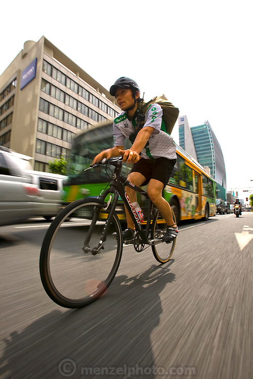 Jun Yajima, a bike Messenger, powers down a busy street in the Shibuya Ward (district) of Tokyo, Japan. (Jun Yajima is featured in the book What I Eat: Around the World in 80 Diets.) MODEL RELEASED.