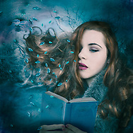 Portrait of a sad young woman with flowing auburn hair reading a book against a soft teal winter background