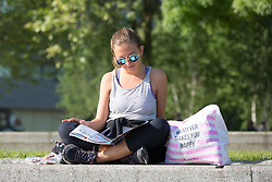 © Licensed to London News Pictures. 08/05/2018. London, UK. A woman reads a magazine in the sunshine and warm weather on the South Bank in London this morning. Photo credit: Vickie Flores/LNP