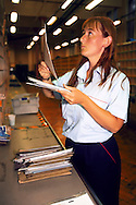 Postwoman sorting letters prior to delivering them on her walk ......