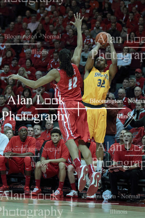 22 January 2014:  Tony Wills challenges a long shot by Tekele Cotton during an NCAA Missouri Valley Conference mens basketball game between the Shockers of Wichita Stat and the Illinois State Redbirds  in Redbird Arena, Normal IL.
