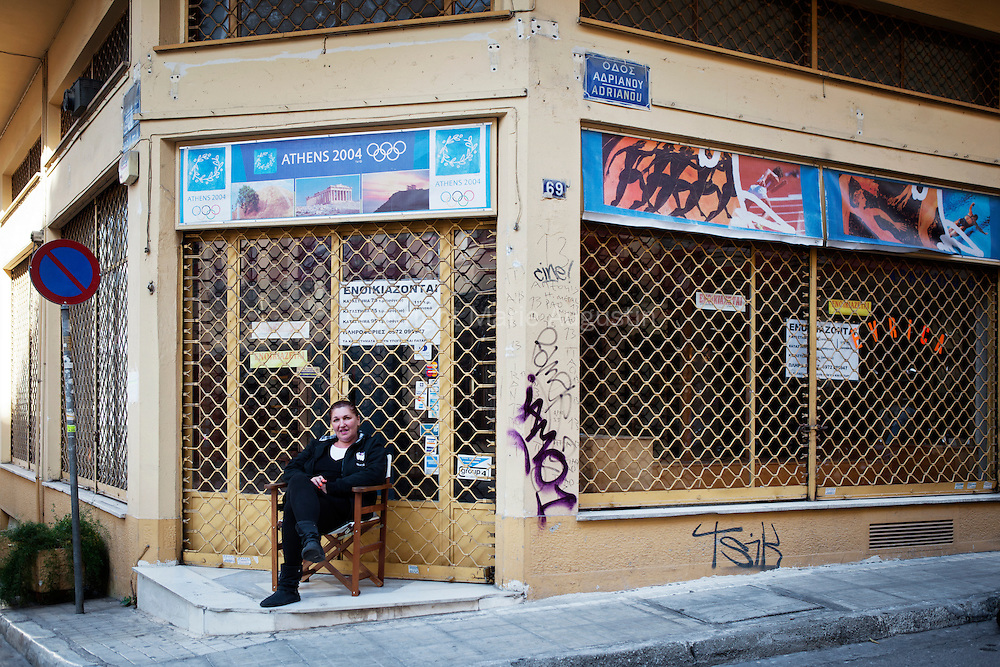 Woman sitting in front of her closed shop in touristic Plaka area - Athens, 28 oct 2011