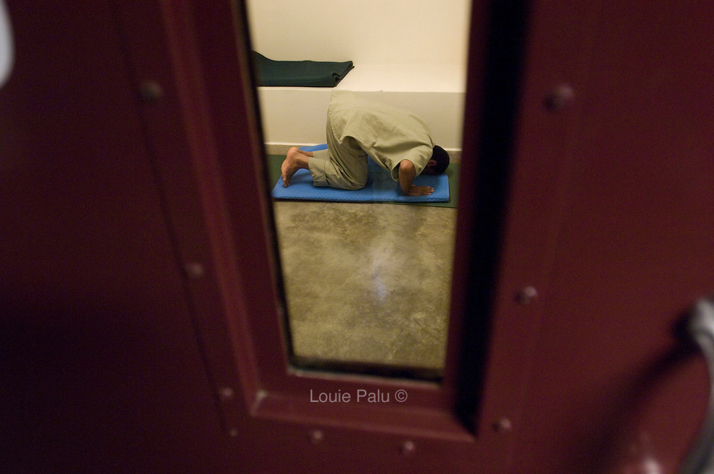 "A detainee prays in his cell in Camp 5, which is a maximum-security detention facility where the most uncooperative as well as detainees with the most intelligence value are housed at the detention facility in Guantanamo Bay, Cuba. Approximately 250 ""unlawful enemy combatants"" captured since the September 11, attacks on the United States continue to be held at the detention facility. (Image reviewed by military official prior to transmission)"