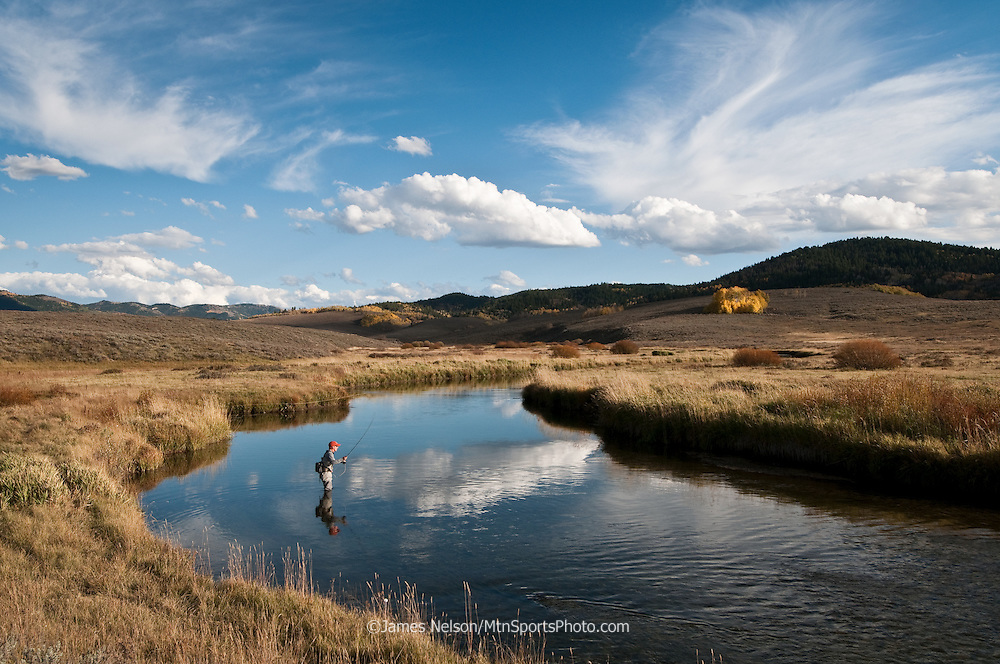 An angler fly-fishes for Yellowstone cutthroat trout at the Blackfoot River Wildlife Management Area in east Idaho during an autumn afternoon.