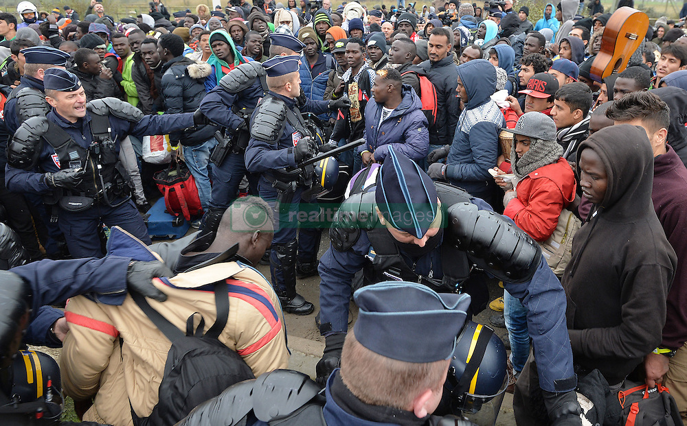 """French police officers go in to stop a fight among a large crowd of migrants as they line-up at a processing centre in """"the jungle"""" near Calais, northern France, as the mass exodus from the migrant camp begins."""