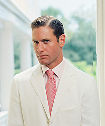 Man with slicked back hair, White jacket and pink tie by a white pillar house