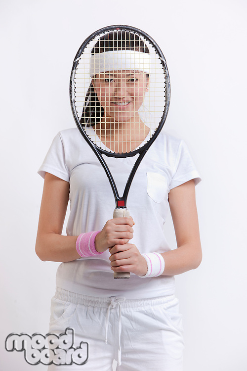 Portrait of young female tennis player holding racket in front of her face against white background