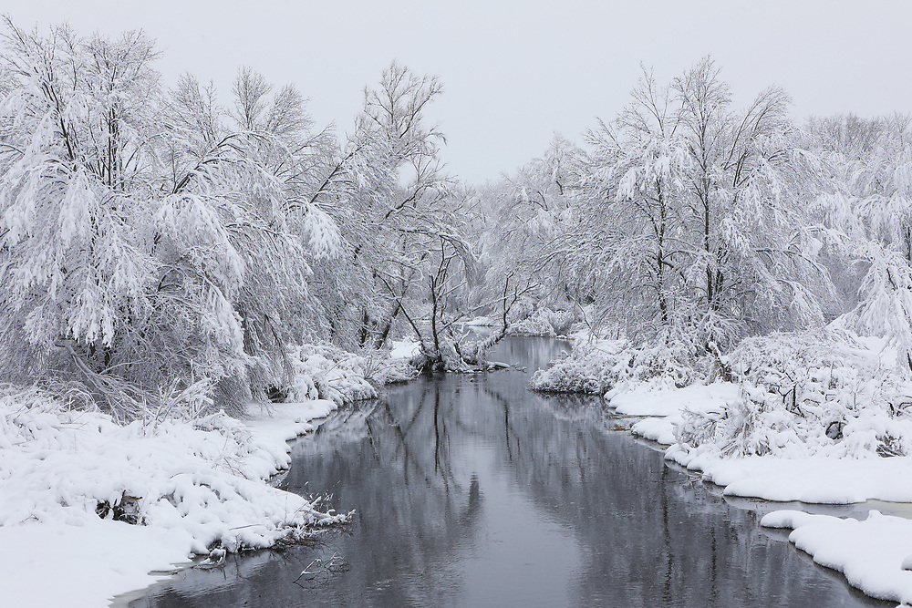 New England Assabet River winter scenery in Westborough Massachusetts during a New England winter snowstorm.<br />