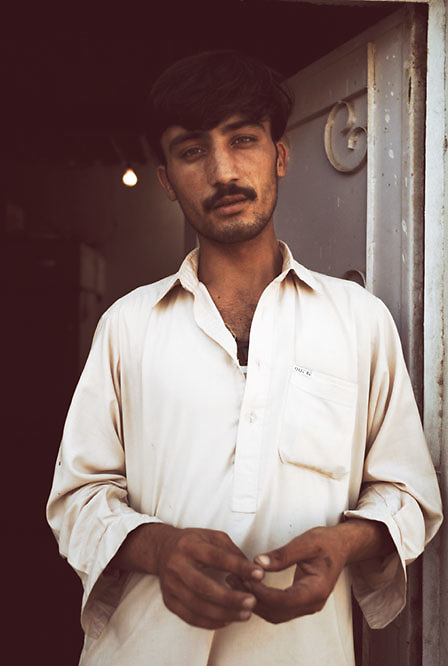 A man stands in a doorway rolling a ball of hash between his fingers at the Smuggler's Bazaar, Khyber-Pakhtunkhwa, Pakistan on 25th Sep, 2007..