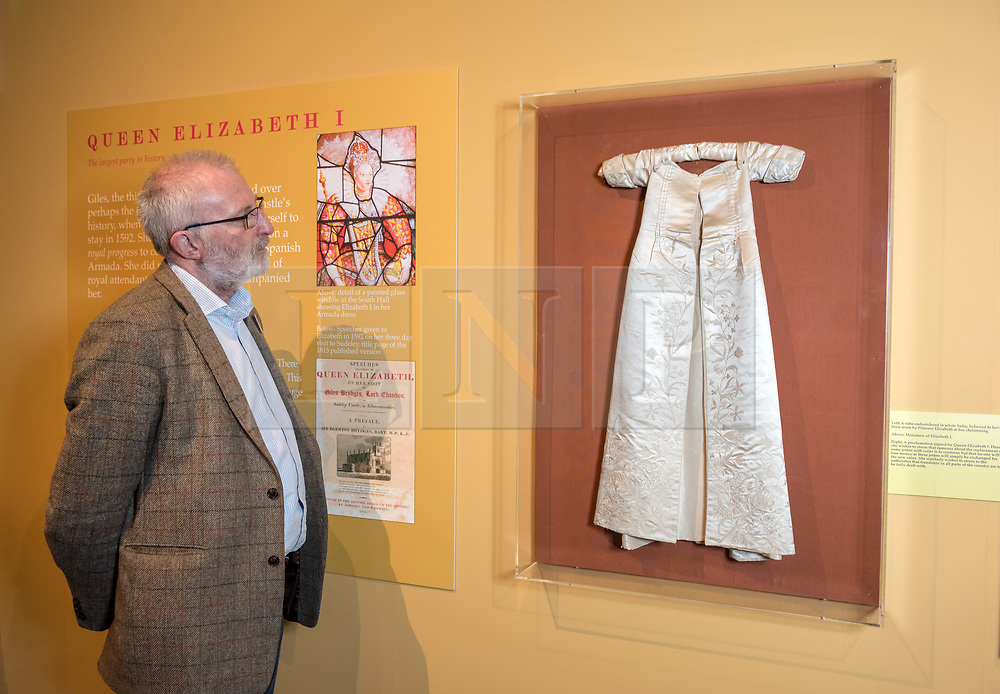 © Licensed to London News Pictures. 16/04/2018. Winchcombe, Gloucestershire, UK. Sudeley Castle's 'Royal Sudeley 1,000, Trials, Triumphs and Treasures'. Picture of DEREK MADDOCK, Sudeley Castle Archivist, with an embroidered christening robe, believed to have been worn by Princess Elizabeth I at her christening. Treasures from Sudeley Castle's 1,000 year history have gone on show in a new exhibition. Called 'Royal Sudeley 1,000, Trials, Triumphs and Treasures', the newly refurbished exhibition includes a collection of priceless objects and curiosities. The exhibition includes a one-of-a-kind, life-size glass-engraved portrait of Katherine Parr by critically acclaimed artist, John Hutton. The artwork was re-discovered during the refurbishment of a holiday cottage on the estate, where it had been for decades. Its importance has now been realised and so it has been brought into the exhibition collection. Numerous items of historic significance are also on display, such as a lock of Katherine Parr's hair, her prayer book and an intricate lace christening canopy believed to have been worked on by Anne Boleyn for the christening of her daughter, Elizabeth I. Sudeley was a royal residence, closely associated with some of the most famous English monarchs, including Edward IV, Richard III, Henry VIII, Lady Jane Grey, Katherine Parr, Elizabeth I and Charles I. The Castle was even home to a secret Queen of England, Eleanor Boteler, whose royal status was unknown for centuries. Photo credit: Simon Chapman/LNP