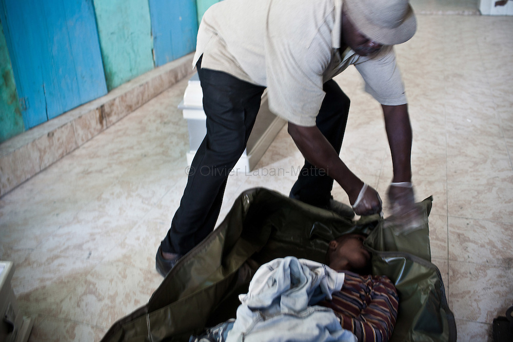 Cholera epidemic, spreading to Haiti last month, finds its source in the Artibonite region, fed by the river of the same name. A municipal employee puts the body of a young boy, died as a result of cholera, in a bag, before throwing it in a mass grave, 11 November 2010 in Gonaïves.