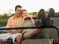 Couple sitting in jeep woman holding binoculars