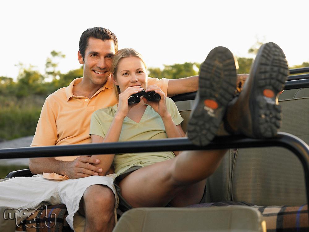 Couple sitting in jeep woman holding binoculars