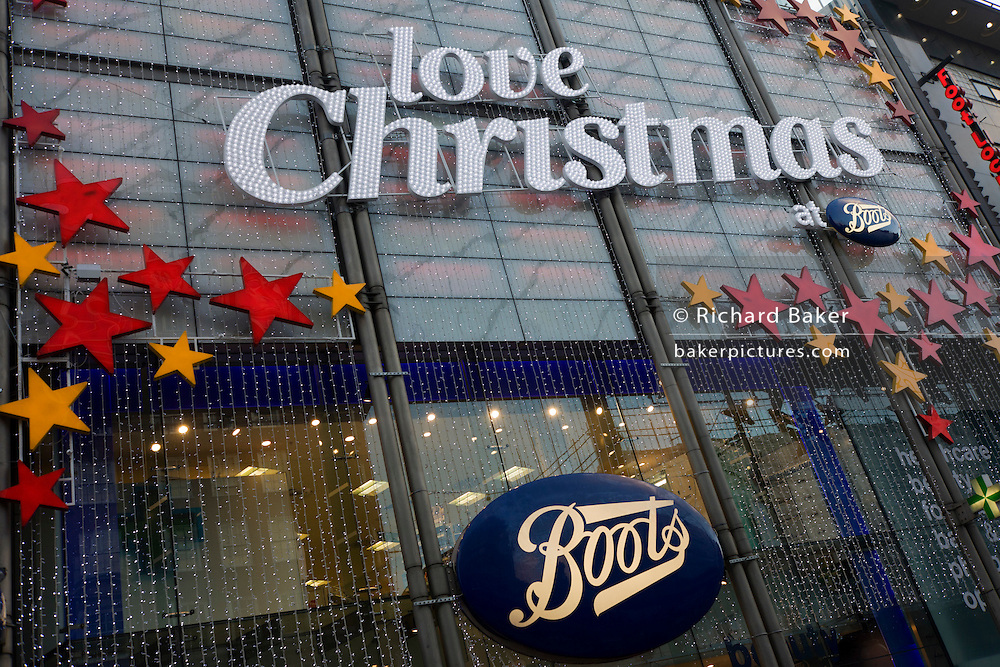 The words 'Love Christmas at Boots' are spread across the frontage window of the Boots branch in London's Oxford Street.
