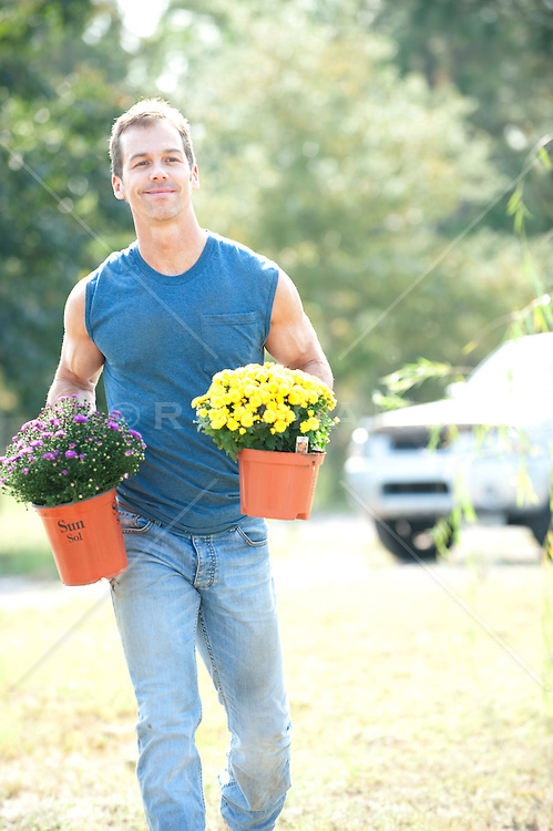 Man carrying two mum plants