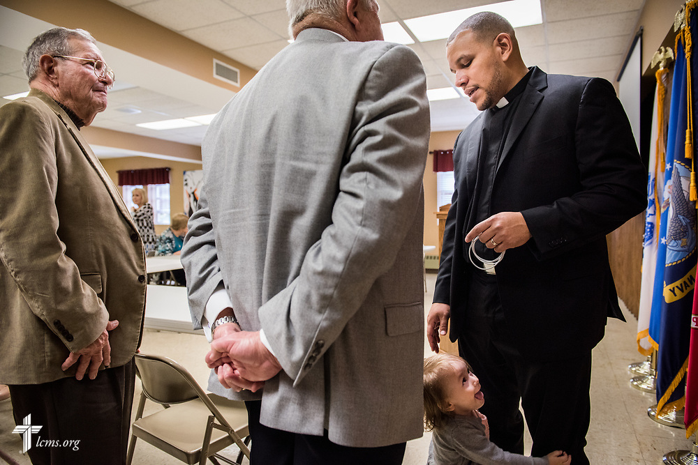 The Rev. Micah Glenn, national missionary to Ferguson, Mo., reaches for his daughter Talitha while thanking supporters Bill Adams and Bill Beggs (left) following Glenn's presentation at Trinity Lutheran Church on Sunday, April 2, 2017, in Cape Girardeau, Mo. LCMS Communications/Erik M. Lunsford