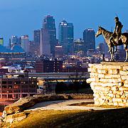 Scout Statue in Penn Valley Park overlooking downtown Kansas City, Missouri skyline at dusk.