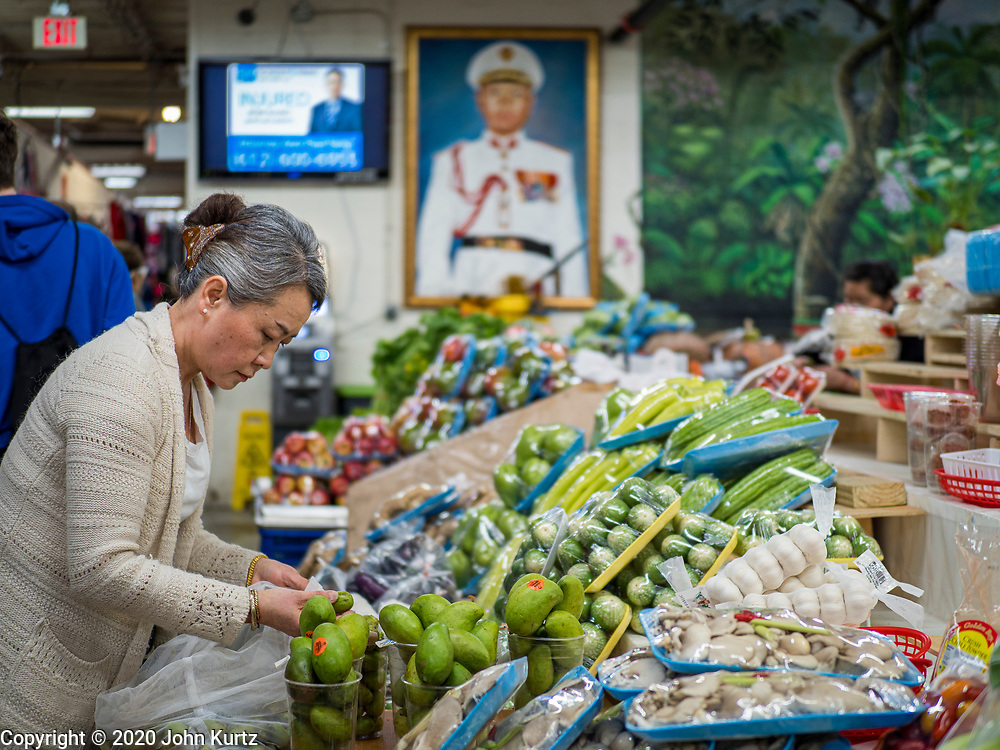 """29 FEBRUARY 2020 - ST. PAUL, MINNESOTA: A woman sets up her vegetable stand in the produce market in the Hmong Village. A portrait of Gen. Vang Pao dominates the room. Vang Pao was a Hmong militay leader who led the Hmong army in the """"Secret War"""" in Laos, when the Hmong were allied with the US against the North Vietnamese. Thousands of Hmong people, originally from the mountains of central Laos, settled in the Twin Cities in the late 1970s and early 1980s. Most were refugees displaced by the American war in Southeast Asia. According to the 2010 U.S. Census, there are now 66,000 ethnic Hmong in the Minneapolis-St. Paul area, making it the largest urban Hmong population in the world. Hmong Village, the largest retail and restaurant complex that serves the Hmong community, has more than 250 shops and 17 restaurants.   PHOTO BY JACK KURTZ"""