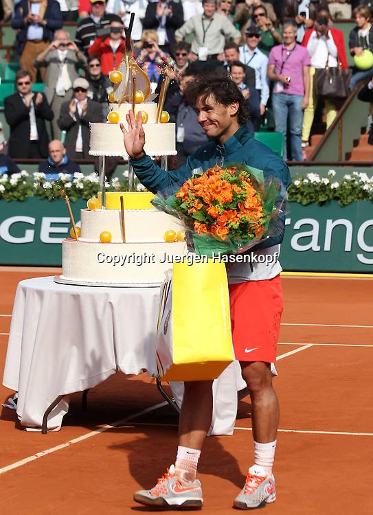 French Open 2013, Roland Garros,Paris,ITF Grand Slam Tennis Tournament,  Geburtstagskind Rafael Nadal (ESP) mit Geschenktuete und Blumenstrauss,im Hintergrund steht die riesige Geburtstagstorte,Ganzkoerper,Hochformat,