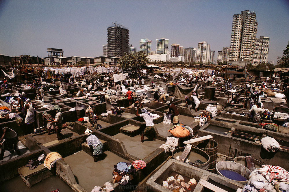 """Washing clothes at the dhobi ghats, Bombay, India. The dhobi is a traditional laundryman, who collects your dirty linen, washes it, and returns it neatly pressed to your doorstep. The """"laundries"""" are called """"ghats"""": row upon row of concrete washtubs."""