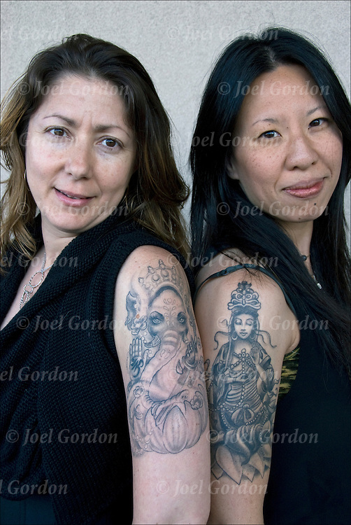 Head and shoulder portraits of partners, Renee and Camellia, and their  tattoos. <br /> <br /> Ganesh or Ganesha the Hindu God has as many meanings, as the god of wisdom, prosperity and good fortune.<br /> <br /> For Renee, Ganesh is the Creator of Aboundance and Remover of Obstacles.<br /> <br /> Kwan Yin is the Goddess of Compassion is on Camellia's right solder.<br /> <br /> Body art or tattoos has entered the mainstream it is known longer considered a weird kind of subculture.<br /> <br /> &quot;According to a 2006 Pew survey, 40% of Americans between the ages of 26 and 40 have been tattooed&quot;.<br /> <br /> releases # 2657 and 2656