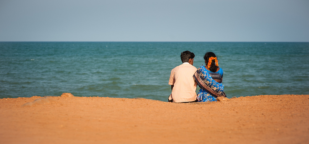 Indian couple sat by the sea at Puducherry (India)
